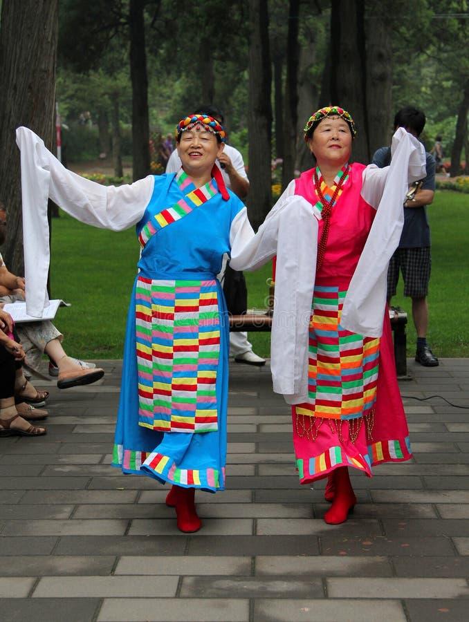 PECHINO, CINA - 17 LUGLIO 2011: Le donne stanno ballando in costumi nazionali nel parco di Jingshan fotografia stock libera da diritti