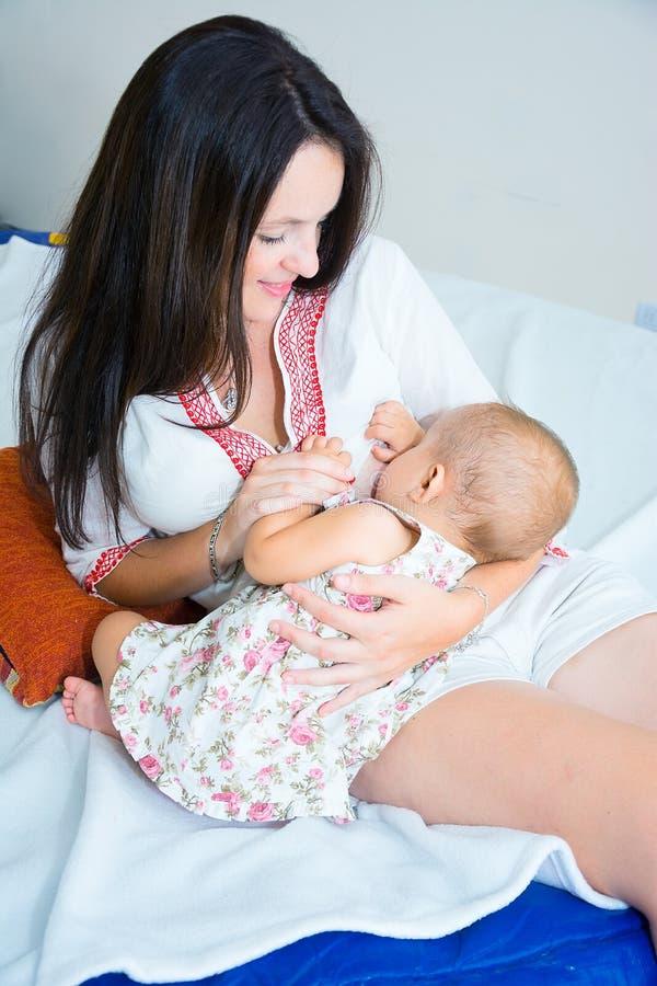 Pecho de alimentación de la madre joven suave de la foto su bebé fotos de archivo
