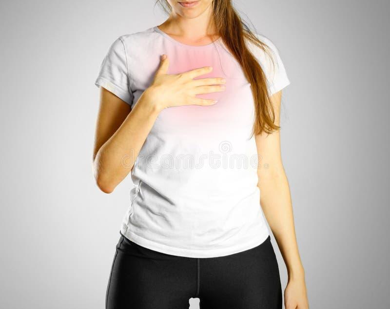 Pechos de la chica joven de un dolor del ` s El dolor en su ardor de estómago del pecho T foto de archivo