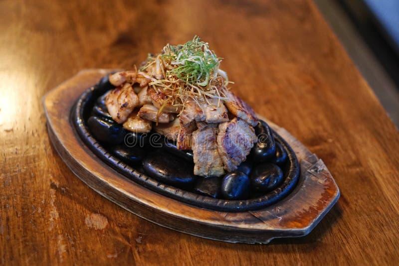 Pechuga de cerdo a la parrilla servida en piedras calientes, con cebollas de primavera cortadas y hoja de romero, al estilo corea imagenes de archivo