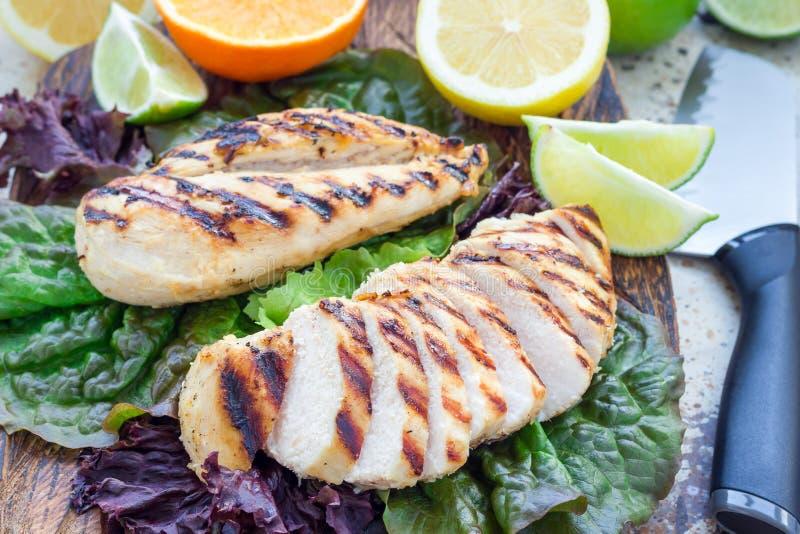 Pechuga de pollo asada a la parrilla en adobo de la fruta cítrica en las hojas de la ensalada y el tablero de madera, horizontale fotografía de archivo