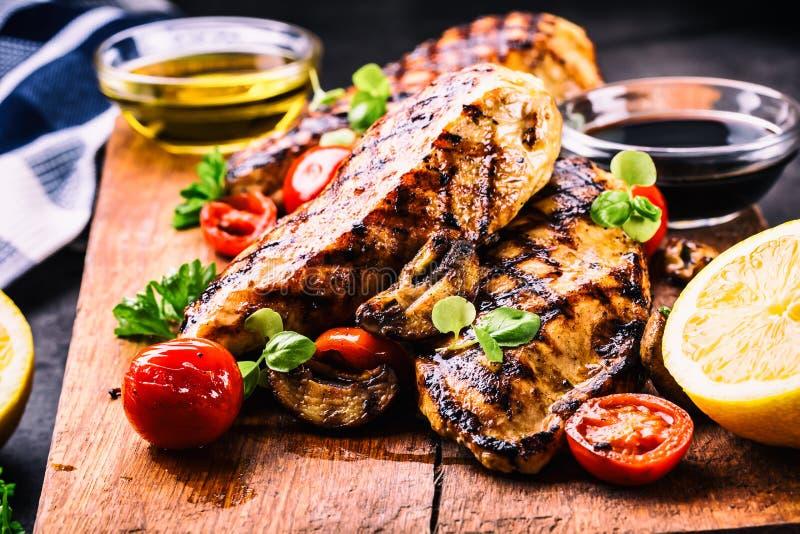 Pechuga de pollo asada a la parrilla en diversas variaciones con los tomates de cereza, las setas, las hierbas, el limón cortado  imagen de archivo libre de regalías