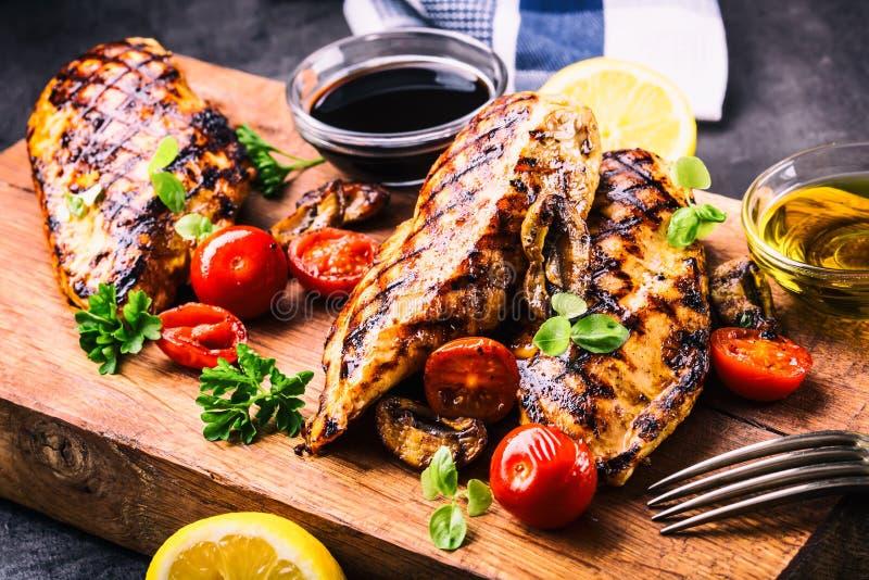 Pechuga de pollo asada a la parrilla en diversas variaciones con los tomates de cereza, las setas, las hierbas, el limón cortado  foto de archivo