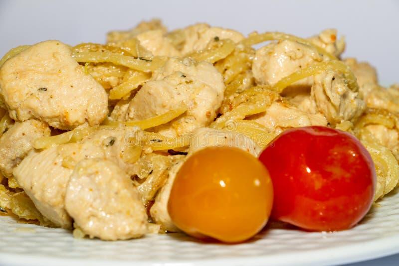 Pechuga de pollo cocida con macarrones hervidos y tomates rojos y amarillos en un fondo blanco imagenes de archivo