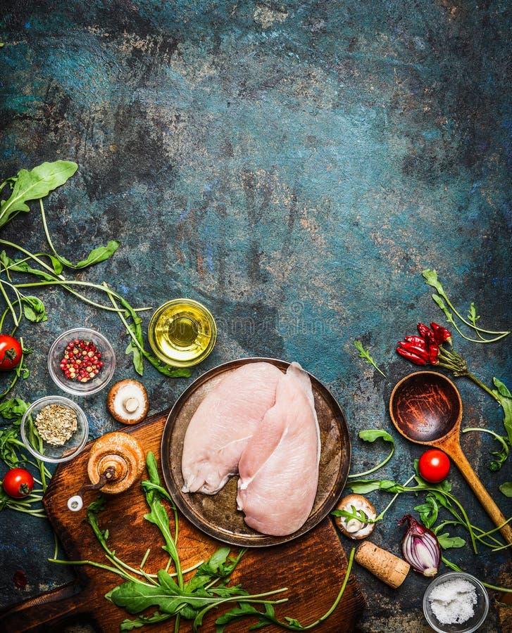 Pechuga de pollo, cuchara de madera e ingredientes deliciosos frescos para cocinar en el fondo rústico, visión superior, marco imagenes de archivo