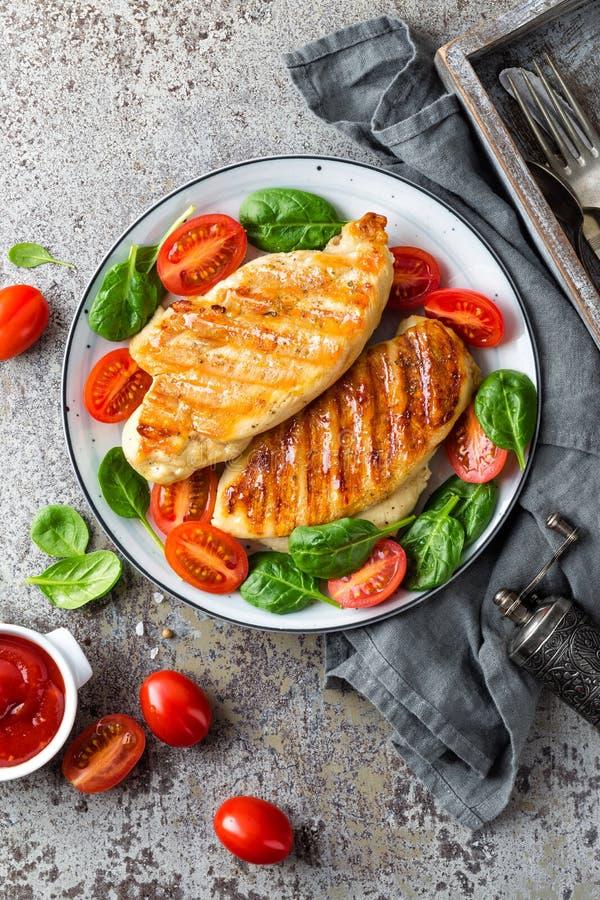 Pechuga de pollo o prendedero, ensalada de las verduras asadas a la parrilla y frescas de la carne de aves de corral del tomate y fotos de archivo