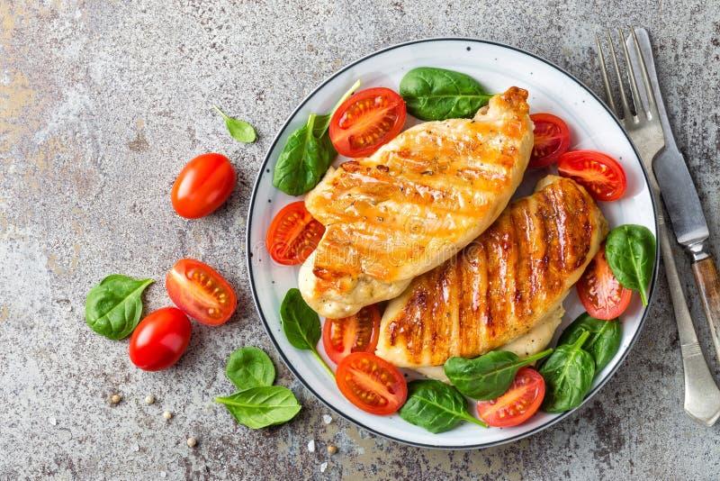 Pechuga de pollo o prendedero, ensalada de las verduras asadas a la parrilla y frescas de la carne de aves de corral del tomate y foto de archivo libre de regalías
