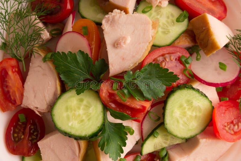 Pechuga de pollo, rábano del pepino y ensalada del tomate con verdes fotografía de archivo