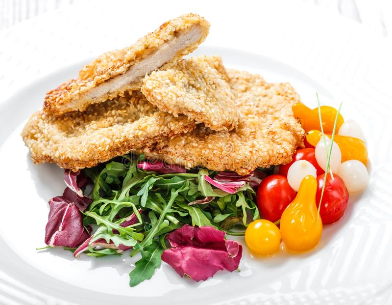 Pechugas de pollo asadas a la parrilla con sésamo, ensalada con la grasa de la col y rucola en fondo de madera ligero fotografía de archivo libre de regalías