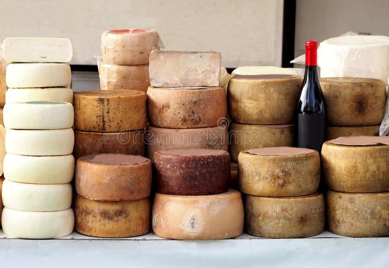 Pecorino乳酪轮子和撒丁岛乳清干酪用在一个室外市场的架子的不同的堆 免版税库存照片