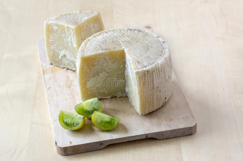 Pecorino cheese on wooden table with cut green zebra tomatoes royalty free stock images