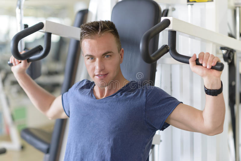 Pectoral Machine. People using pectoral machine at gym royalty free stock photography