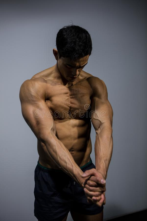 Pectoral Muscle Flexing. A fitness model flexing his pectoral muscles. Medium shot royalty free stock photo