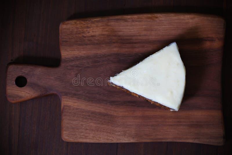 Pedaço de bolo com crosta de gelo branca do maçapão, em uma placa de madeira imagens de stock royalty free