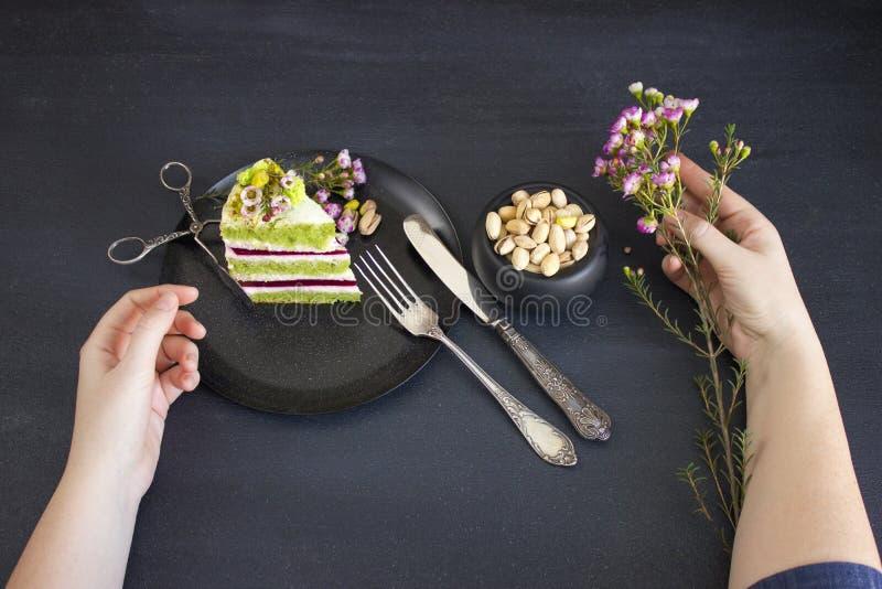 Pedaço de bolo com enchimento e pistaches da framboesa imagem de stock