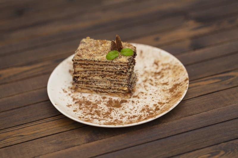 Pedaço de bolo Napoleon na placa branca Culinária do russo, bolo mergulhado com creme do chocolate fotografia de stock