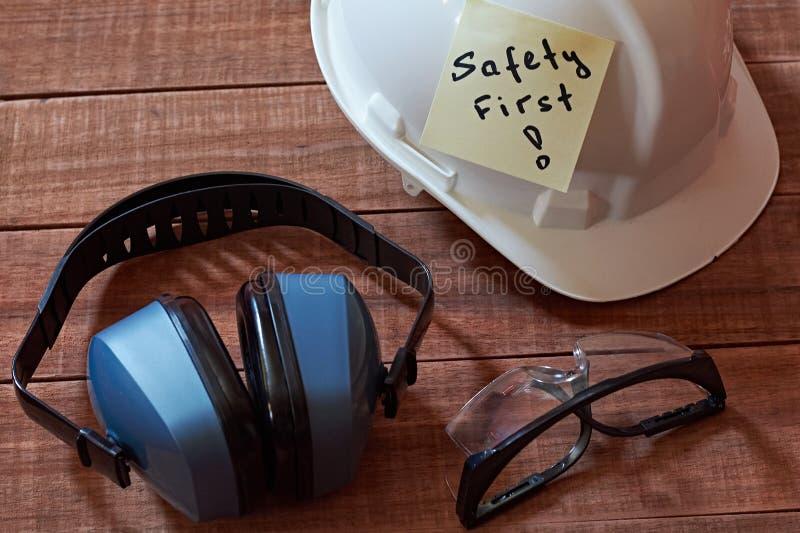 Pedaço de papel amarelo da nota uma da segurança em primeiro lugar colado no fundo de madeira com conjunto completo de equipament foto de stock royalty free