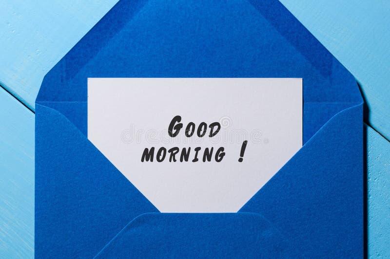 Pedaço de papel com BOM DIA do texto no envelope azul no close-up de madeira da tabela fotos de stock royalty free