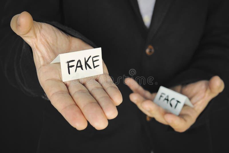 pedaço de papel com a inscrição falsa na mão de um homem sobre o fundo de outra mão com o fato de inscrição O conceito fotografia de stock royalty free