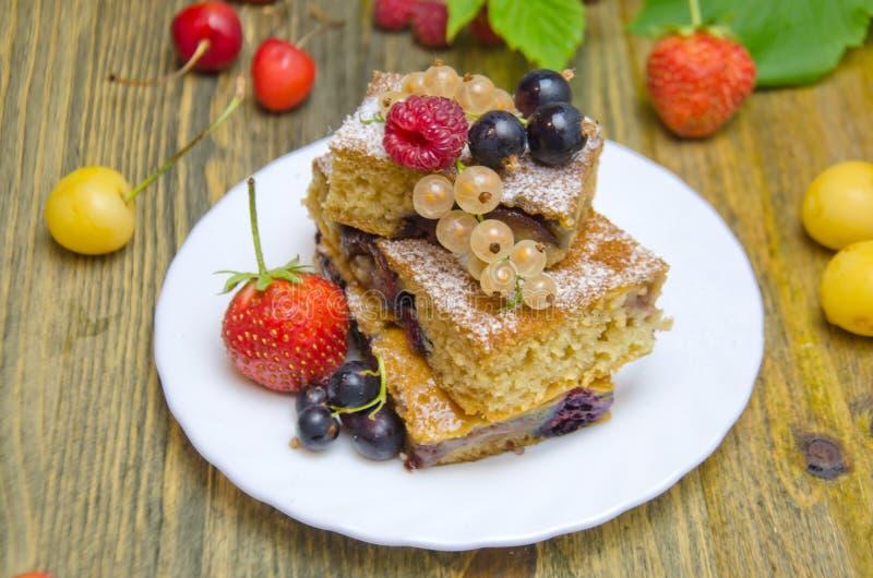 Pedaços de bolo com bagas e as bagas frescas do corinto e da cereja da morango no fundo de madeira fotografia de stock