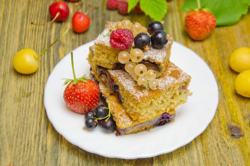 Pedaços de bolo com bagas e as bagas frescas do corinto e da cereja da morango no fundo de madeira foto de stock