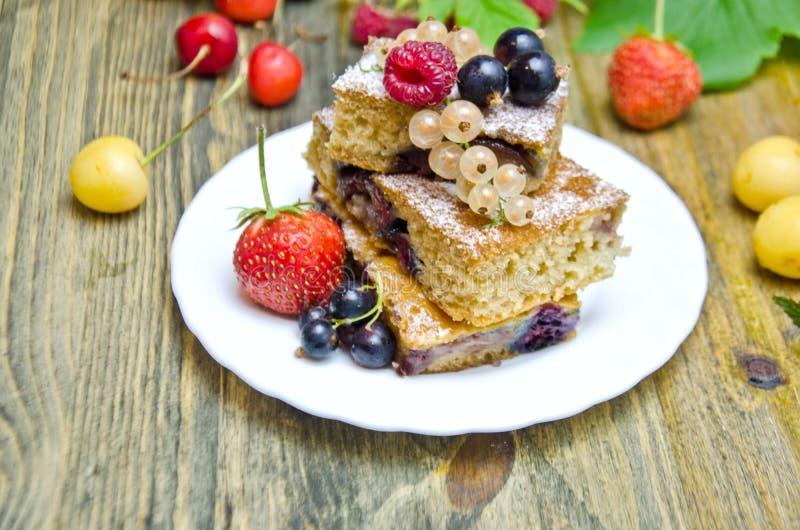 Pedaços de bolo com bagas e as bagas frescas do corinto e da cereja da morango no fundo de madeira imagem de stock