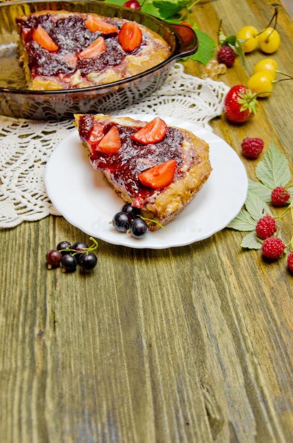 Pedaços de bolo com bagas e as bagas frescas do corinto e da cereja da morango no fundo de madeira imagens de stock royalty free