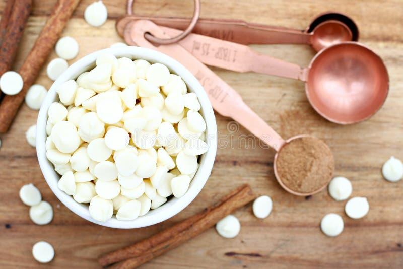 Pedaços de chocolate & colheres de medição brancos imagens de stock royalty free