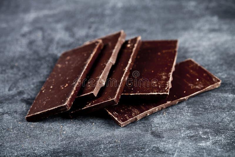 Pedaços de chocolate escuro quebrado empilhado no fundo cinzento imagens de stock royalty free