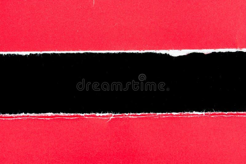 Pedaços de papel de papel vermelhos do rasgo no preto fotografia de stock royalty free