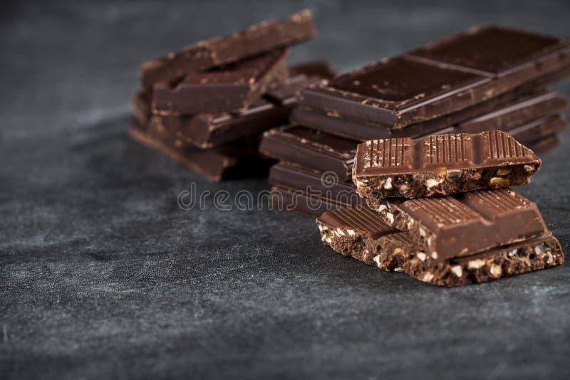 Peda?os de chocolate quebrado empilhados na placa preta imagem de stock