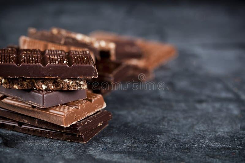 Peda?os de chocolate quebrado empilhados na placa preta Pilha das partes das barras de chocolate no fundo preto imagem de stock royalty free
