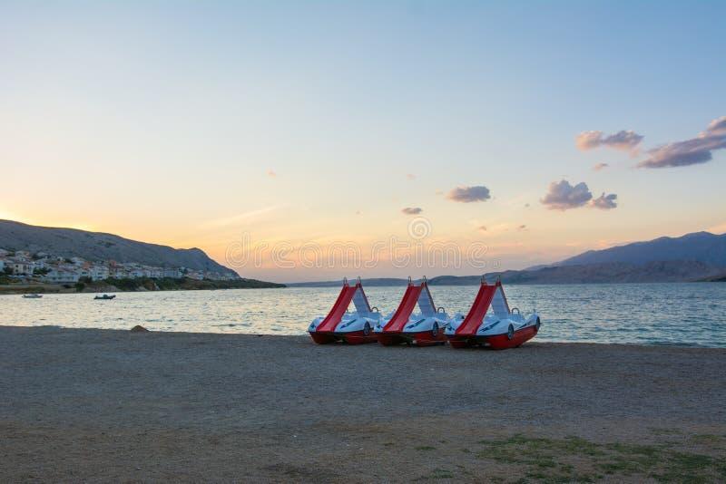 Pedaalboten op het strand bij zonsondergang royalty-vrije stock foto