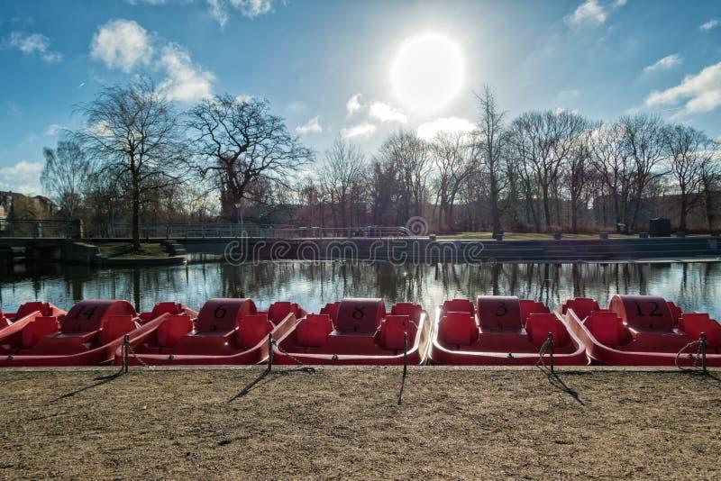 Pedal- röda stakbåtar i den Odense floden, Danmark royaltyfri bild