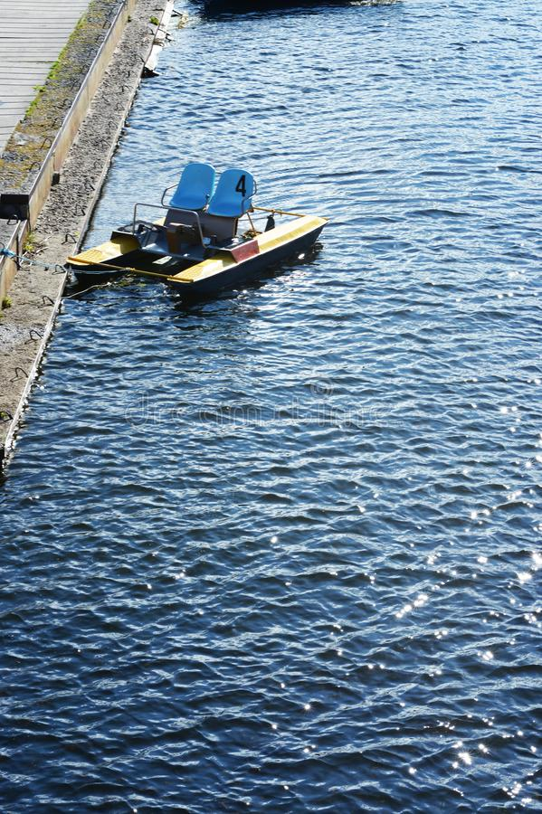 A pedalo on the rough surface of a blue river at the pier. stock photography
