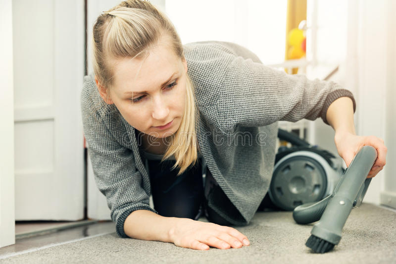 Pedantic woman cleaning house with vacuum cleaner. Pedantic woman on knees cleaning house with vacuum cleaner royalty free stock photos