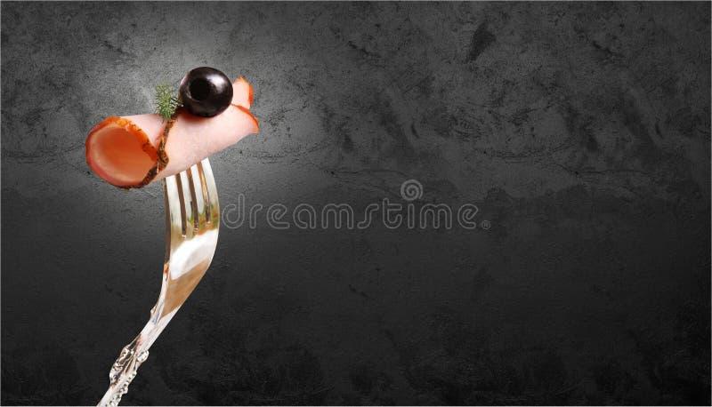 Pedazo apetitoso de carne ahumada con la aceituna y una puntilla del eneldo fijada en una bifurcación contra una pared de piedra  fotografía de archivo libre de regalías