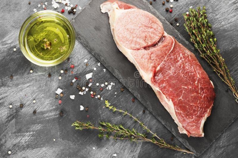 Pedazo de carne cruda de la carne de vaca en un tablero de la pizarra con pimienta, aceite de oliva y un tomillo en un fondo oscu imagenes de archivo