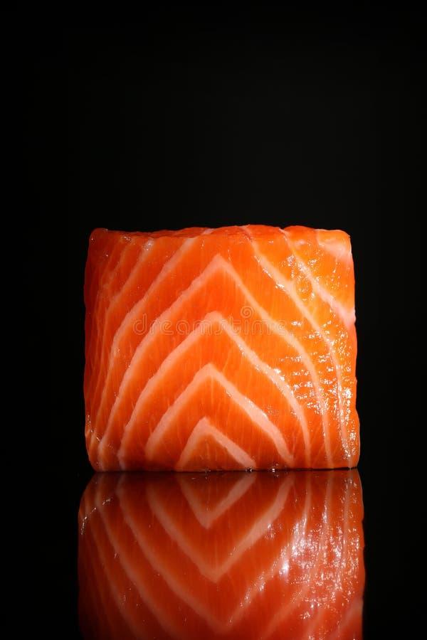 Pedazo de color salmón fresco aislado en fondo negro con la reflexión imagen de archivo