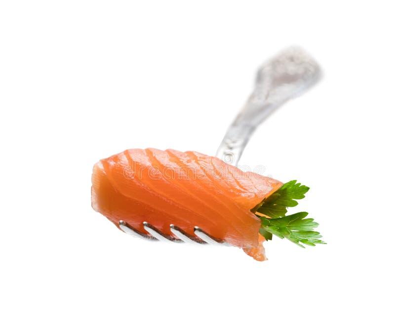 Pedazo de color salmón rodado con la hoja del perejil en la bifurcación aislada en blanco fotos de archivo libres de regalías