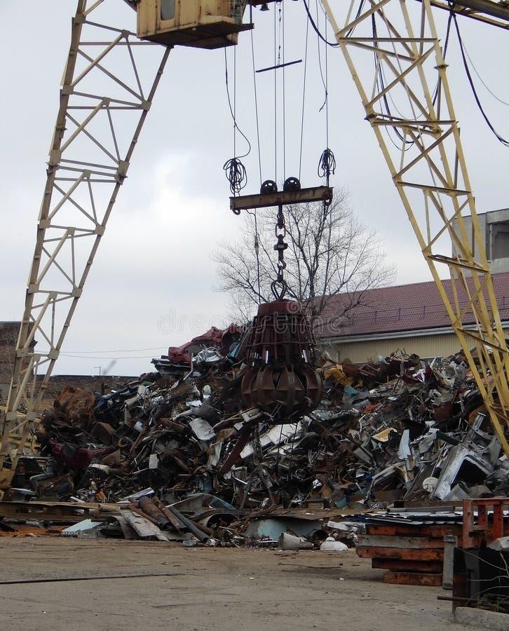 Pedazo de Crane Machine Loading Rusty Metal del capturador en el Scrapyard imagenes de archivo