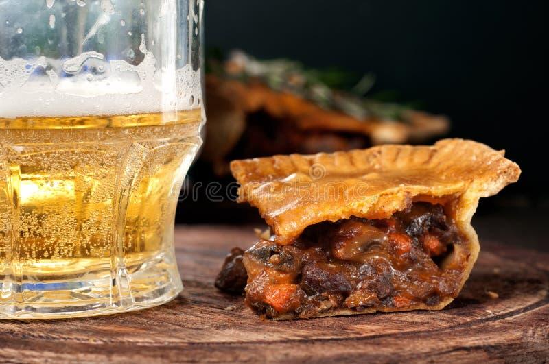 Pedazo de empanada de carne australiana con una cerveza ligera de cristal imagen de archivo libre de regalías