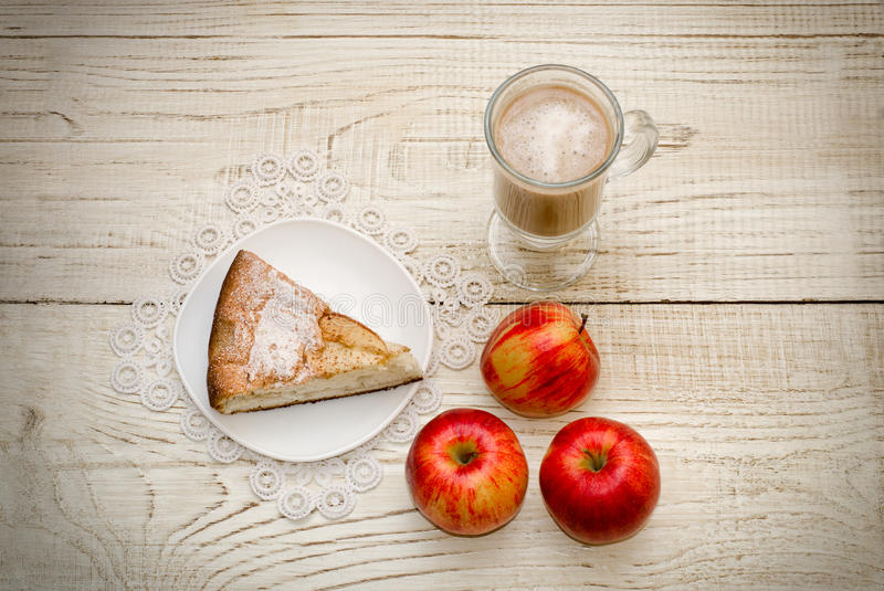 Pedazo de empanada de manzana, de capuchino y de manzanas maduras en un fondo de madera ligero imágenes de archivo libres de regalías