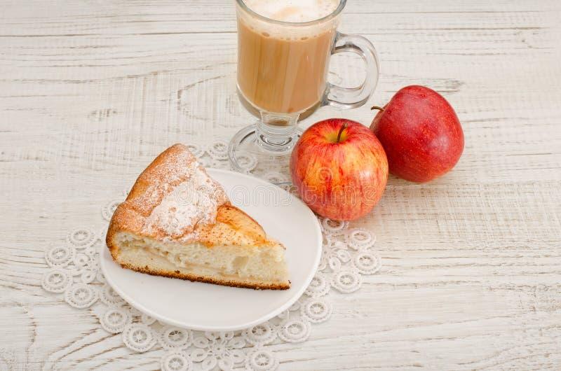 Pedazo de empanada de manzana, de capuchino y de manzanas maduras en un fondo de madera ligero, visión superior imágenes de archivo libres de regalías