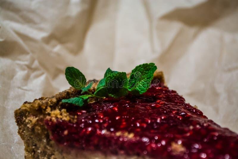 Pedazo de empanada fresco con el atasco de la frambuesa con una rama de la menta en el papel del arte Tazas de café y granos de c fotografía de archivo