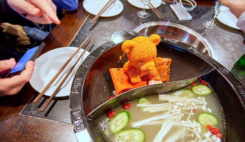 Pedazo de fusión de Orande de grasa formado como figura del oso en el plato caliente de acero para cocinar de la comida china tra foto de archivo