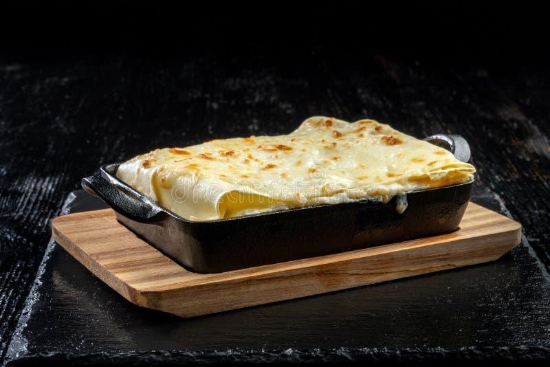 Pedazo de lasa?as calientes sabrosas Lasañas italianas tradicionales en una cacerola del arrabio  fotos de archivo