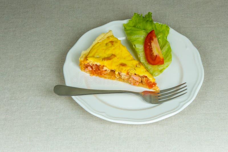Pedazo de pasta de hojaldre agria hecha en casa rellena con la salchicha, tomate imagen de archivo libre de regalías