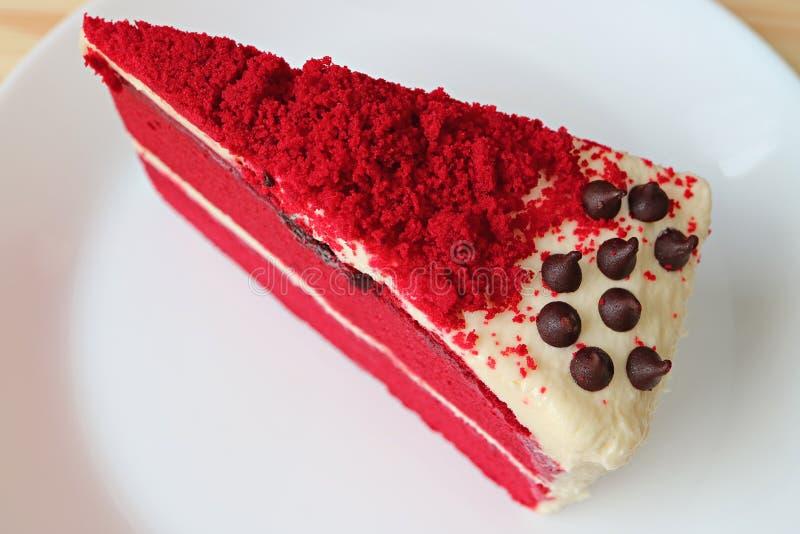 Pedazo de pastel de capas rojo del terciopelo con el queso cremoso que hiela en una placa blanca fotografía de archivo libre de regalías