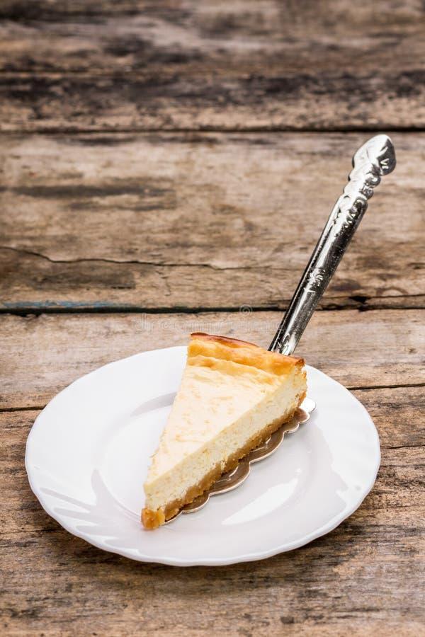 Pedazo de pastel de queso con el servidor de la torta en la tabla de madera imagen de archivo libre de regalías